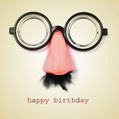 sentence happy birthday and fake eyeglasses, nose and mustache on a beige background, with a retro e