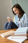 Cheerful teenage girl looking at mobile phone home read funny SMS