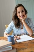 Teenage student girl studying at home smiling leaning against table