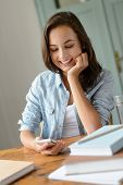 Smiling teenage girl looking at mobile phone studying at home