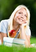 Dreaming woman lying on the green grass near red apple on the pile of books. Pleasant atmosphere of