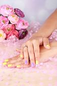 Female hand with stylish colorful nails, on color fabric background