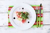 Salad with watermelon, feta, arugula, shrimps, balsamic sauce  on plate, on wooden background