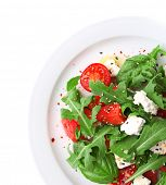 Salad with watermelon, feta, arugula and basil leaves on plate, isolated on white