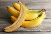 Halved and whole ripe bananas on wooden background