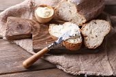 Fresh bread and homemade butter on wooden background