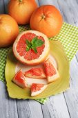 Ripe grapefruits on plate on color wooden background