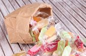 Tasty candies in paper bag on wooden background