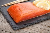 Fresh salmon fish with lemon on wooden table
