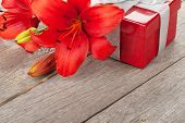 Red lily flower and gift box on wooden table with copy space