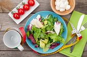 Fresh healthy salad, tomatoes, mozzarella on wooden table. Healthy food