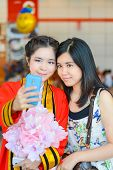 Graduate Thai college student from King Mongkut's institution taking photograph with her friend