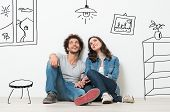 stock photo of couples  - Portrait Of Happy Young Couple Sitting On Floor Looking Up While Dreaming Their New Home And Furnishing - JPG