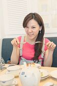 Asian woman eat lunch with funny face.