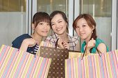 Group of Asian women shopping and holding shopping bags.