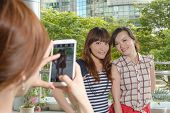 Asian woman take photos by smartphone.