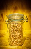 Brow Rice In A Glass Bottle In Blurry Wood Background