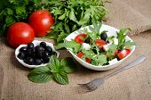 Greek Salad In White Salad Bowl With Cutlery And Vegetables Around