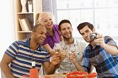 Group of friends making self portrait of themselves, smiling happy, drinking at home.