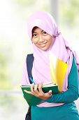 image of muslim kids  - Portrait of happy muslim kid student writing something on book  - JPG