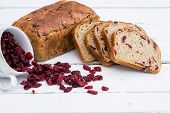Bread with cranberries on white wooden board.