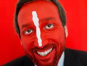 Conceptual portrait of adult man with colorful red painted face and white line on nose