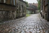 An old wet cobbled street with rows of houses along the way