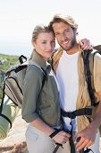 Attractive hiking couple smiling at camera on mountain trail on a sunny day