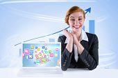 Excited redhead businesswoman sitting at desk against blue bar chart with blue arrow