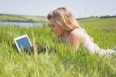 Pretty blonde lying on grass using her tablet on a sunny day in the countryside