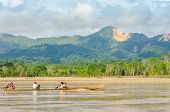 RURRENABAQUE, BOLIVIA, MAY 11, 2014 - Local people travel in traditional wooden boat on Beni river