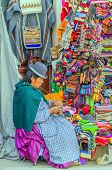 LA PAZ, BOLIVIA, MAY 9, 2014 - Local woman in traditional costume and bowler hat sits in front of he