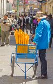 LA PAZ, BOLIVIA, MAY 8, 2014 - Street seller of ice cream sells his merchandise on busy Comercio str
