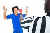 Serious referee showing red ard to player on white background