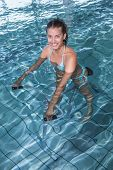 Fit brunette using underwater exercise bike in swimming pool at the leisure centre