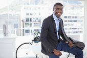 Smiling businessman with his bicycle in his office