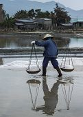 One Woman Carries Two Baskets Filled With Freshly Harvested Salt.
