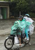 Family Of Four Travel In The Rain On Motorbike.
