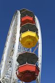 Low angle view of multicolored Ferris wheel in amusement park against blue sky