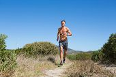 Shirtless man jogging with heart rate monitor around chest on a sunny day