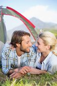 Attractive couple lying in their tent about to kiss on a sunny day