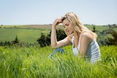 Pretty blonde thinking while sitting on grass on a sunny day in the countryside