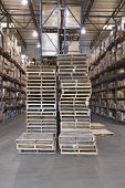 Wooden pallets and cardboard boxes stacked in distribution warehouse