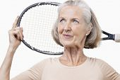 Senior woman holding tennis racket over her shoulder against white background