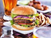stock photo of chicken  - hamburger with fries and beer shot in panorama style with chicken wings in background - JPG