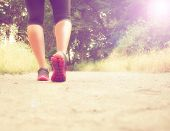 an athletic pair of legs running or jogging on a path during sunrise or sunset