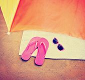 the top of an umbrella and pink flip flop sandals and sunglasses toned with a retro vintage instagr
