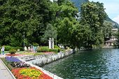 LUGANO, SWITZERLAND - JULY 5, 2014: People stroll along the shoreline in the Parco Ciani. The area h