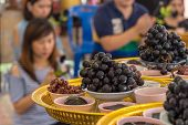 Nakornpathom, Thailand - Jul 5, 2014 : Grapes And Many Black Thing To Give To