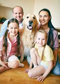 A young friendly family of four and their pet looking at camera